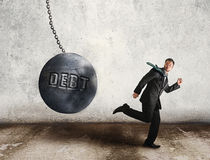 Escape the debt. Young businessman running away from the wrecking ball, as the symbol of debt Stock Images
