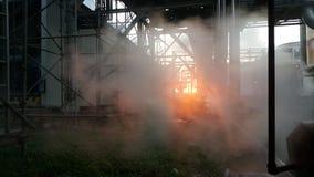 Escape del vapor en industial detrás de fondo de la puesta del sol fotografía de archivo