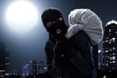 Escape enmascarado del ladrón en la noche fotos de archivo