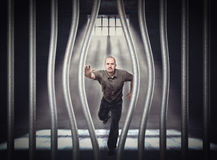 Escape from jail. Man try to escape from jail with bended bar royalty free stock image