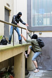 Escape from a robbery. One tries to help another to climb the rails Royalty Free Stock Images