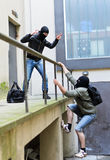 Escape from a robbery. One tries to help another to climb the rails Stock Images