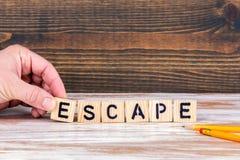 escape Träbokstäver på kontorsskrivbordet arkivbild