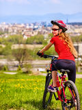 Escape urban . Bicycle girl wearing helmet rest from city urbanization. Royalty Free Stock Photo
