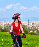 Escape urban . Bicycle girl wearing helmet rest from city urbanization. Escape urban . Bicycle girl has rest from city bustle. Woman wearing sport helmet rides Stock Photos