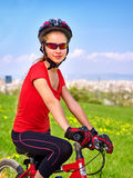 Escape urban . Bicycle girl wearing helmet rest from city urbanization. Escape urban. Bicycle girl has rest from city bustle. Woman wearing sport helmet rides Royalty Free Stock Photography
