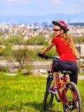 Escape urbano Monte en bicicleta el resto del casco de la muchacha que lleva de la urbanización de la ciudad Foto de archivo libre de regalías