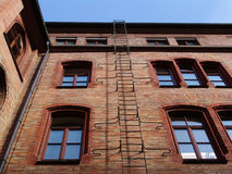 Escape way. Fire-escape on an old building with walls made of bricks royalty free stock images