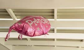 Escaped balloon in the rafters. A pink party balloon floats up in the rafters in a roof image with copy space royalty free stock image