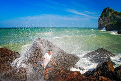 Escaping big wave. Man escaping incoming big wave on the coast in Thailand stock photo