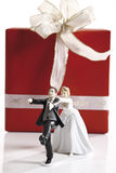 Escaping Bride Groom figurine in front of wedding present Stock Photo