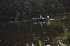 Escaping from the city. Beautiful young couple enjoying romantic date while rowing a boat royalty free stock photography