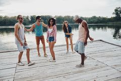 Escaping from the city. Full length of happy young people in casual wear smiling and gesturing while enjoying beach party royalty free stock images