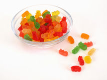 Escaping the Den. A small candy dish full of brightly colored candy bears. A few are laying loose to the side, over a white background Royalty Free Stock Photography