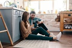Escaping from everything. Beautiful young couple drinking wine while sitting on the kitchen floor at home royalty free stock image