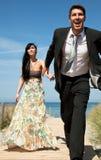 Escaping honeymoon couple on the beach Stock Photos