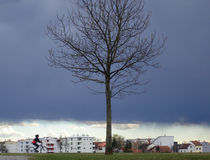 Escaping from storm. Girl riding bike on stormy day Stock Images