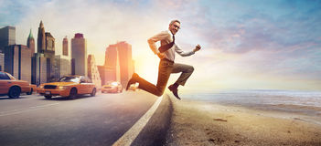 Escaping from town. Young businessman escaping from town headed to the beach royalty free stock image