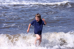 Escaping the waves. Happy 6-8 years boy playing on the beach and trying to escape waves Royalty Free Stock Photos