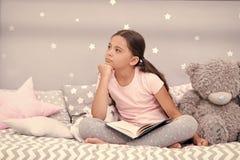 Escapistconcept Leuk weinig escapist De droom van het escapistmeisje in bed Kindescapist met boek en teddybeer Kinderjarendroom royalty-vrije stock afbeeldingen