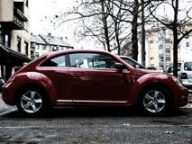 Escarabajo brillante de VW del rojo en estacionamiento fotografía de archivo