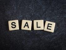Escarafunchar telhas da letra na venda preta da soletração do fundo da ardósia fotos de stock