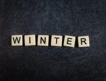 Escarafunchar telhas da letra no inverno preto da soletração do fundo da ardósia imagem de stock royalty free