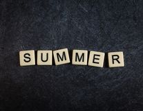 Escarafunchar telhas da letra no verão preto da soletração do fundo da ardósia imagens de stock