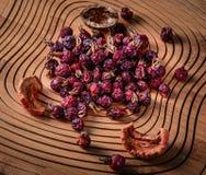 Escaramujos y frutos secos secos en un tablero de madera Imagen de archivo