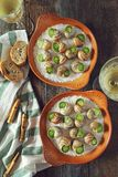 Escargots, traditional French cuisine: snails sauce Burgundy and. A glass of white wine. Top view, toned image stock photos