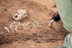 Escavações Archaeological O arqueólogo em um processo do escavador Feche acima das mãos com pesquisa de condução sobre os ossos h imagem de stock