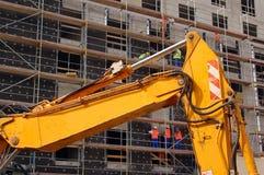 Escavador e trabalhadores da construção amarelos fotos de stock