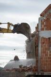 Escavador mecânico que demole uma construção imagens de stock