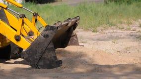 A escavadora amarela enfileira a areia na cubeta filme