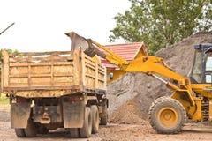 A escavadora amarela escavava o solo no caminhão. Fotos de Stock