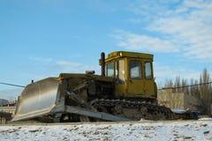 Escavadora amarela suja na estrada do inverno porque construção parada foto de stock