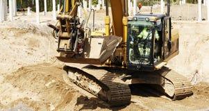Escavadora e motorista na ação Fotografia de Stock Royalty Free