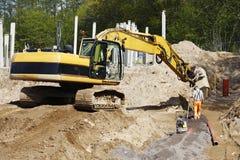 Escavadora e trabalhador do local na ação Fotografia de Stock Royalty Free