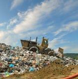 A escavadora em uma descarga de lixo Fotografia de Stock Royalty Free