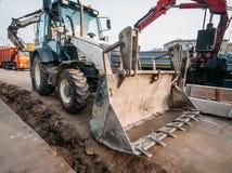 A escavadora hidráulica pequena para o reparo da rua funciona, maquinaria industrial moderna foto de stock