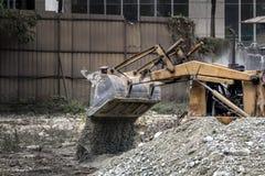 A escavadora no canteiro de obras derrama a entulho toned imagem de stock