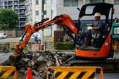 Escavando acima a estrada e a substituição do equipamento e da tubagem fotografia de stock royalty free