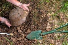 Escavando na floresta o capacete alemão M35 imitation Recuperação WW2 Rússia imagens de stock royalty free