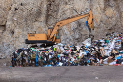 Escavator at garbage dump Stock Photos