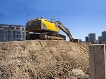 Escavatore al cantiere in costruzione contro il cielo blu - immagine con lo spazio della copia fotografia stock