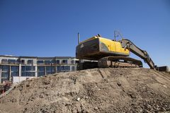 Escavatore al cantiere in costruzione contro il cielo blu - immagine con lo spazio della copia immagine stock libera da diritti