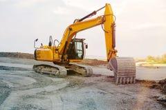 Escavatore al cantiere della via sulla campagna immagine stock