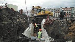 Escavatore alla sabbia dello scarico del cantiere dentro alla fossa con due lavoratori in caschi archivi video