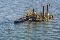 Escavatore che draga sulla piattaforma di galleggiamento Immagini Stock Libere da Diritti