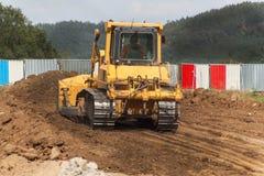 Escavatore che lavora ad un cantiere Bulldozer giallo della costruzione sul lavoro Costruzione di nuova strada Fotografie Stock Libere da Diritti